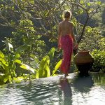 Woman walking by the pool belonging to one of the villas at the Damai, Bali