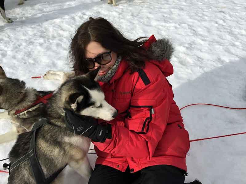 Karin is cuddling a sled dog.