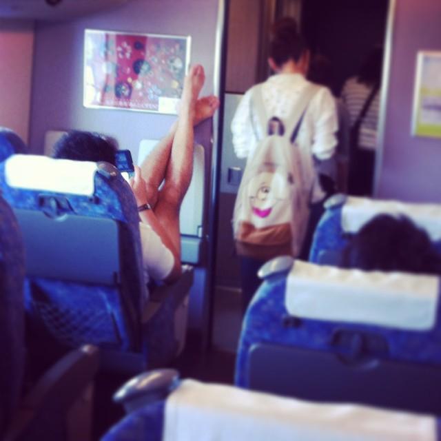 Naked feet against bulkhead on plane.