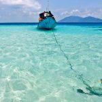 Boat anchored in the crystal clear waters of Karimunjawa where Kura Kura Resort is located.