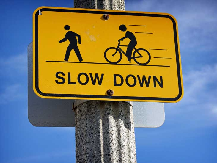 Follow road signs and traffic laws as a cyclist.