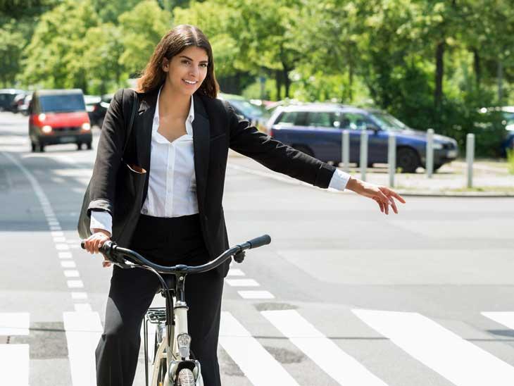 Woman on bike signalling turn.