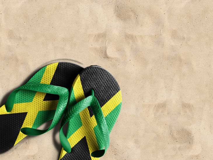 Slippers in the Jamaican colors on beach sand.
